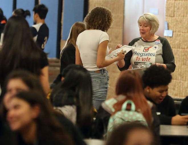 Becky Drotz hands out voter registration paperwork to students during lunch at Bremerton High School on Feb. 28. The League of Women Voters have been holding registration drives at high schools, where 16- and 17-year-olds can now register to vote.