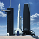 A SpaceX rendering shows pad 39A with the existing service tower to the left with the proposed new mobile service tower to the right. The new tower would allow for vertical integration of Falcon rockets. This rendering also shows Falcon Heavy with an extended length payload fairing.