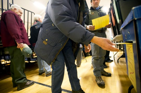 Residents cast their ballots just before the start of town meeting at Charlotte Central School in March 2013.