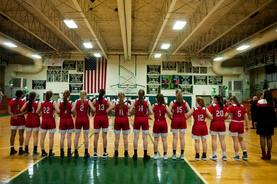 The teams listen to the national anthem during the girls basketball game between the Champlain Valley Union Redhawks and the Rice Green Knights at Rice Memorial High School on Thursday night February 27, 2020 in South Burlington, Vermont.