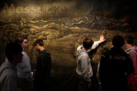 Eighth grade students from St. Joseph School in Cold Springs, Ky., touch a relief image created with bullet casings at the Holocaust & Humanity Center inside the Cincinnati Museum Center in Cincinnati on Wednesday, Feb. 5, 2020.