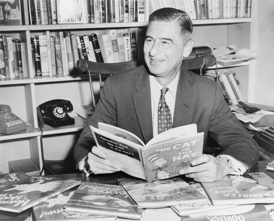Ted Geisel, aka Dr. Seuss, is seated at desk covered with his books.