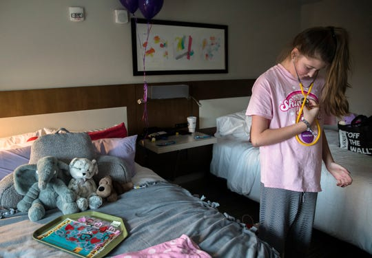 Hope Weaver, 13, listens to her heart with her stethoscope while unpacking her belongings in a hotel room on Monday, Feb. 17, 2020 in Evanston. Weaver stayed there after receiving a heart transplant at Cincinnati Children's Hospital Medical Center.