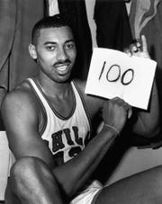 "March 2, 1962: Philadelphia Warriors' Wilt Chamberlain holds a sign reading ""100"" in the dressing room in Hershey, Pa., after he scored 100 points as the Warriors defeated the New York Knickerbockers 169-147."