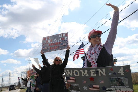 Jessica Breznican, right, and other protesters wave signs and flags across the road from the Mike Bloomberg rally at Old Glory Distilling Co., in Clarksville, Tenn., on Friday, Feb. 28, 2020.