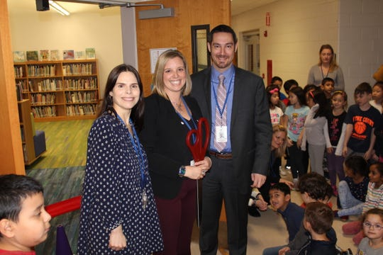 Lindsay La Neve, library media specialist; Alison Tugya, principal; and Dr. Matthew Mingle, superintendent, take a quick picture just before the ribbon-cutting ceremony for the Central School Library.