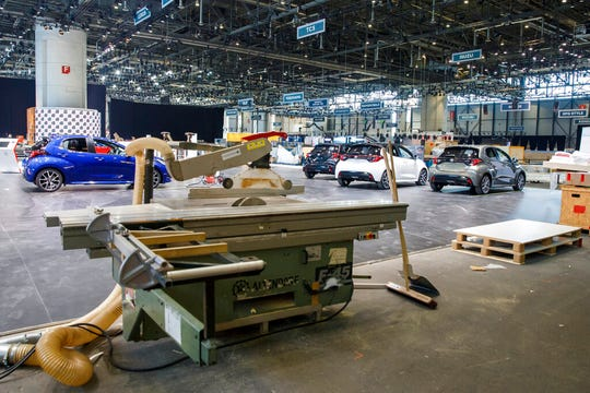 Cars are pictured as workers stop the preparation of the 90th Geneva International Motor Show, GIMS, at Palexpo, in Geneva, Switzerland, Friday, Feb. 28, 2020. The 90th edition of the International Motor Show, scheduled to begin on March 5th, is cancelled due to the advancement of the (Covid-19) coronavirus in Switzerland.