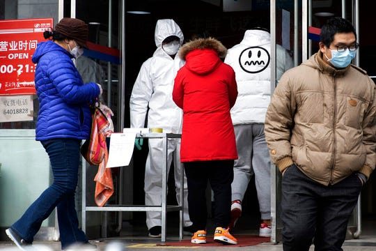 In this Thursday, Feb. 27, 2020, file photo, a worker in overalls screen for fever at the entrance to a supermarket in Beijing. Health officials reported the first U.S. drug shortage tied to the viral outbreak that is disrupting production in China, but they declined to identify the manufacturer or the product.