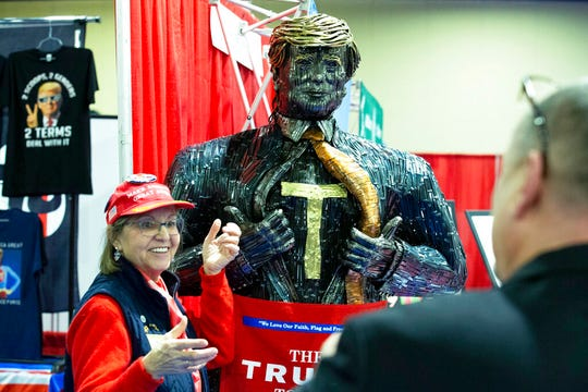 A supporter of President Trump poses for a photo next to a figure during CPAC 2020.