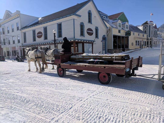A team of horses haul lumber to a construction site along the deserted Main Street in the dead of winter on Mackinac Island.
