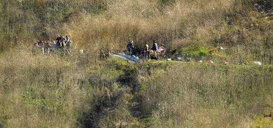 Investigators work the scene of a helicopter crash that killed former NBA basketball player Kobe Bryant, his 13-year-old daughter, Gianna, and seven others on a hillside in Calabasas, Calif. on Jan. 27, 2020.