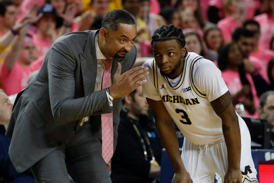 """""""So far, so good. Everyone is fine. I'm just keeping my prayers and staying on my knees that stays consistent,"""" says Michigan coach Juwan Howard, here speaking with Zavier Simpson."""