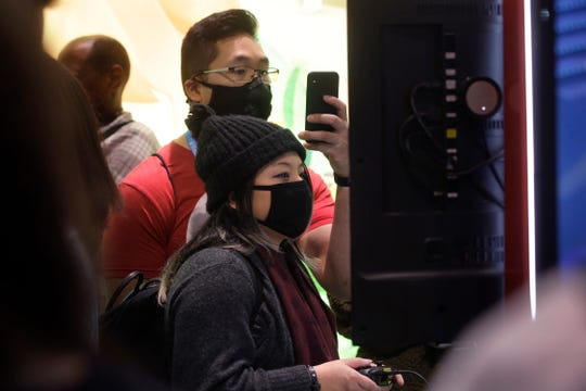 Sonya Tran, of Randolph, Mass., front, and Bobby Ratanasim, of Providence, R.I., behind center, wear protective masks while playing a Nintendo game, Thursday at the Pax East conference in Boston. Tran and Ratanasim said concerns about the coronavirus played a role in wearing masks to the conference.