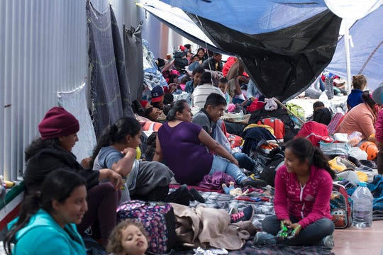 People who traveled from Central America rest to wait for access to request asylum in the US, outside the El Chaparral port of entry building at the US-Mexico border in Tijuana, Mexico, in this April 30, 2018, file photo.