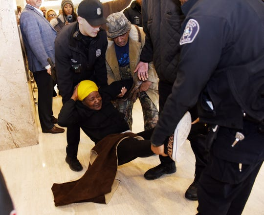"Agnes Hitchcock, 74, of Detroit, the leader of ""Call 'Em-Out"" group is escorted out of the Detroit Finance Department-Income office by Detroit police during a protest inside City Hall."