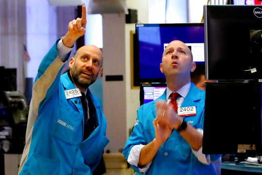 Specialists Meric Greenbaum, left, and Jay Woods work on the floor of the New York Stock Exchange on Friday amid turmoil in the markets.