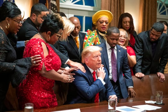 African American leaders say a prayer with President Donald Trump as they end a meeting in the Cabinet Room of the White House, Thursday, Feb. 27, 2020, in Washington.