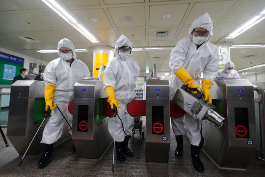 Workers wearing protective gears spray disinfectant as a precaution against the new coronavirus at a subway station in Seoul, South Korea, Friday.