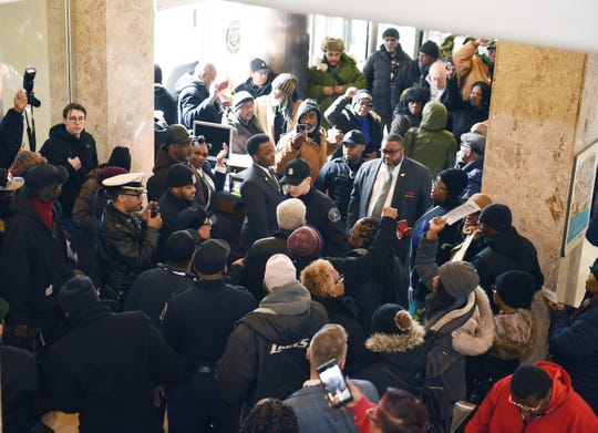 "The group ""Call' Em-Out"" protests the City of Detroit overtaxation on the first floor inside city hall."