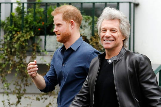 Britain's Prince Harry, the Duke of Sussex, left, walks along with musician Jon Bon Jovi as he leaves Abbey Road Studios in London, Friday, Feb. 28, 2020. The Prince met musician Jon Bon Jovi and members of the Invictus Games Choir, who are recording a special single in aid of the Invictus Games Foundation.