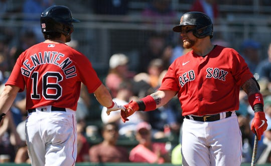 Boston Red Sox left fielder Andrew Benintendi is congratulated after scoring a run by teammate Christian Vazquez in the third inning of the game against the Philadelphia Phillies at JetBlue Park.