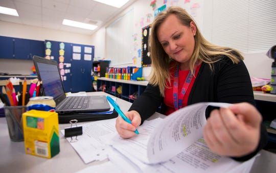 Meagan Griffin, 28, a second-grade teacher at James Stephens International Academy, grades assignments Wednesday afternoon, 2/26/20, during her planning period. Griffin had to take on a second job as a dining room server in a local nursing home in order to afford Southwest Floridahousing costs.