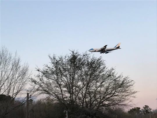 Those gathered outside of the North Charleston Coliseum cheer and snap pictures as Air Force One flies overhead, Friday, Feb. 28, 2020.