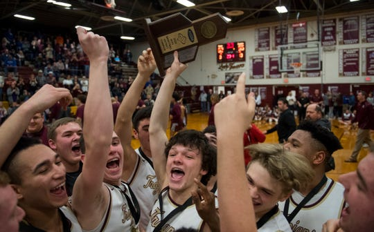 The Webster County Trojans celebrate their victory over the Henderson County Colonels in the Sixth District championship basketball game at Webster County High School in Dixon, Ky., Thursday evening, Feb. 27, 2020.
