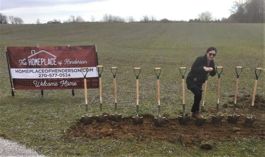 Economic development staffer Whitney Risley works on trying to get ceremonial shovels to stay in the ground at Friday morning's groundbreaking for The Homeplace of Henderson.