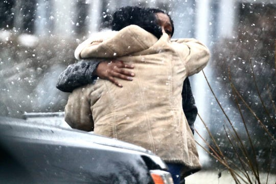 Two women embrace each other near a death investigation in the 1400 block of Pruitt Street in Indianapolis, Friday, Feb. 28, 2020.