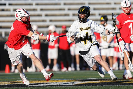 Cornell Big Red men's lacrosse short stick midfielder Harrison Bardwell (No. 17) makes a play against Towson attacker Tim Montgomery (No. 44) as Cornell Michael Long (No. 1) looks on during a game in Baltimore on Friday, Feb. 21, 2020.