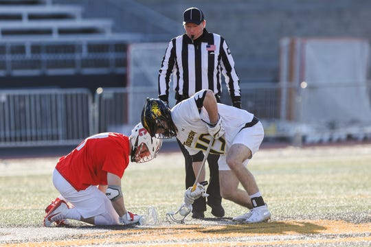 Cornell Big Red men's lacrosse senior Paul Rasimowicz competes in a faceoff against Towson midfielder Jack McNallen during a game in Baltimore on Friday, Feb. 21, 2020.