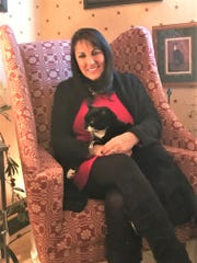 Colony Classics & Interiors owner Janet Muralt is show here with her cat, Mr. Belle. She opened the business at 602 N. High St. in October 1984.