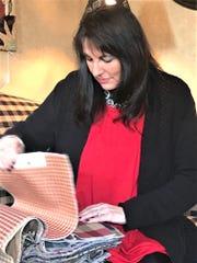 Colony Classics & Interiors owner Janet Muralt looks through fabric samples.