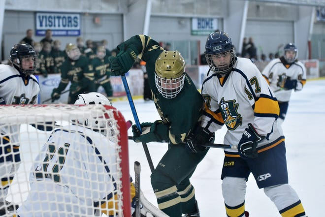 Howell's Nathan Peterson battles in front of goalie Tyler Krasofsky with Marcus Lossia (17) of Walled Lake Central-Waterford in a regional hockey game on Thursday, Feb. 27, 2020.