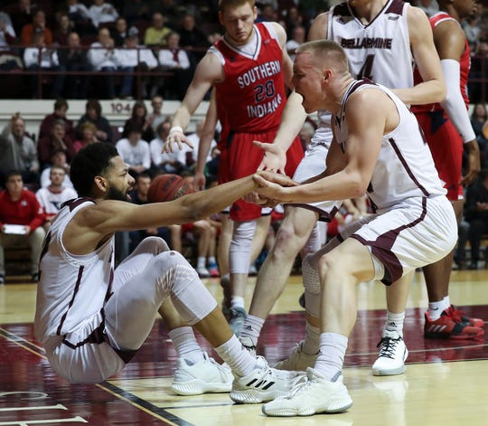 Bellarmine's CJ Fleming (25) helped teammate Pedro Bradshaw (32) to his feet after he scored against Southern Indiana during their game at Knights Hall in Louisville, Ky. on Feb. 27, 2020.