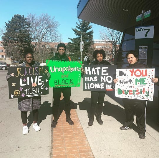 Jonathan Suan, far right, displays a poster with other students during the Black Student Alliance Commemoration March on Friday, Feb. 21, 2020, at Michigan State University. The march commemorated Lansing's only lynching victim and publicized recent racial bias incidents at MSU. Suan said Asian students are now being discriminated against and isolated as a result of the spread of the Coronavirus.