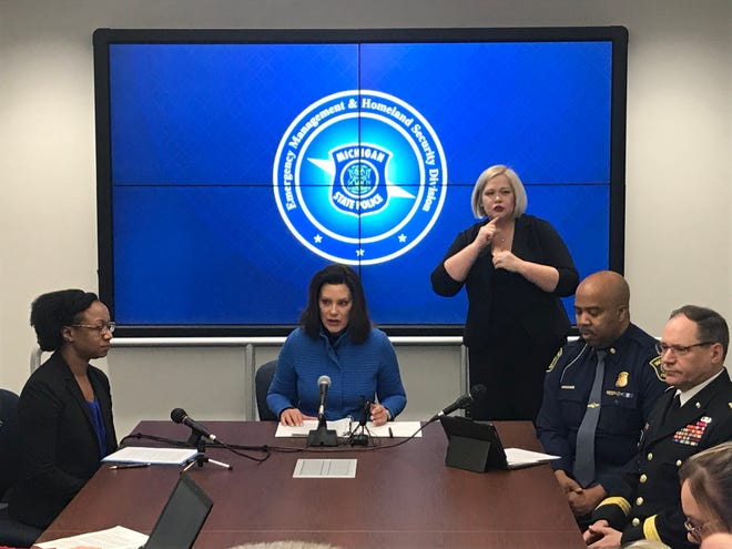 Gov. Gretchen Whitmer, center, announces she opened the state Emergency Operations Center on Friday to prepare for the coronavirus to reach Michigan. She was joined by MDHHS Chief Medical Executive Joneigh Khaldun, left and Michigan State Police Captain Emmitt McGowan, seated immediately to her right.