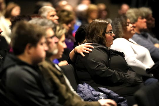 Church members comfort one another as they listen to Pastor Mark Weigt at The Ridge Community Church in Greenfield.