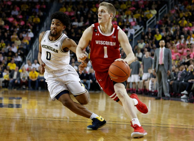Badgers guard Brevin Pritzl dribbles on Michigan Wolverines guard David DeJulius in the second half at Crisler Center.