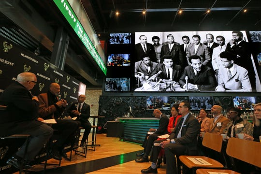 """While photos from the career of Kareem Abdul-Jabbar are shown, he talks with Jim Paschke, left, and Grady Crosby, right at the """"Diversity and Inclusion Conversation,"""" at the MECCA Sports Bar and Grill on Friday. Among the people in the large photo on the screen with Abdul-Jabbar, right, are Bill Russell, from left,  Muhammad Ali and Jim Brown."""
