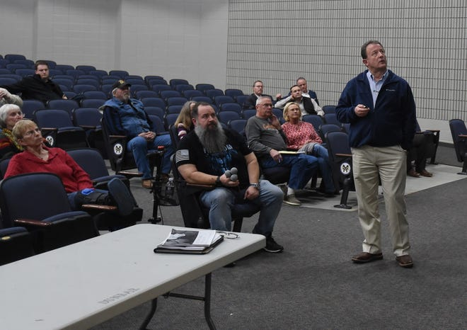 Mountain Home Mayor Hillrey Adams (standing) uses a remote control on Thursday night to flip through several slides outlining the city's proposed $36 million parks improvement plan. That plan would include building a community/aquatic center at McCabe Park.