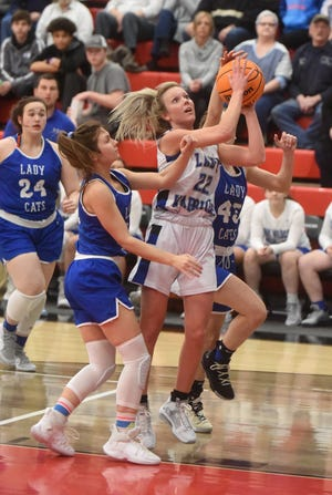 Cotter's Kaylee Crownover goes between two Hector defenders during the Lady Warriors' 53-52 loss Thursday night at Eureka Springs.