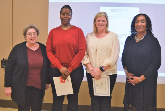 Montgomery County Board of Education President Clare Weil, left, and Superintendent Ann Roy Moore, right, help honor Tiffany Smith, second from left, and Jennifer Noah at the February 25, 2020, board meeting.