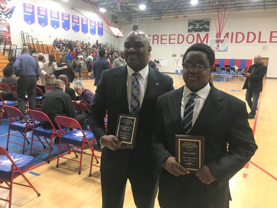 The 14th Annual Booker Award recipients are Dr. Damien Hodge, Sr., who accepted the community award and eighth grader James Onadeko, who accepted the student award at Freedom Middle School.