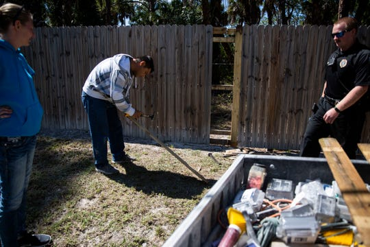 Ernesto Rubio, center, repairs a fence along Rock Road that was damaged when someone cut through to get to the Dorias' property near Golden Gate Estates on Friday, February 28, 2020.