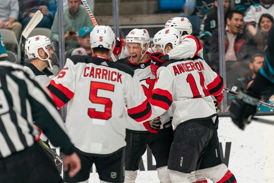 Feb 27, 2020; San Jose, California, USA;  New Jersey Devils center John Hayden (15) and New Jersey Devils right wing Joey Anderson (14) and New Jersey Devils center Travis Zajac (19) and teammates celebrate after the goal during the first period at SAP Center at San Jose.