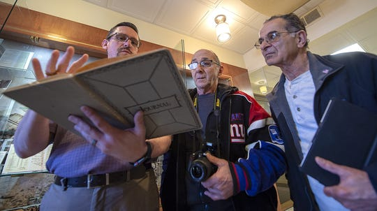 James Warrick, (from the left), 87th Air Base Wing, historian, goes over the journal with Lafayette BelBol, of Parsippany, and his cousin, Michael Hilway, of Woodland Park, as they view the display of the donated items  in the Wing Headquarters Building at Joint Base-McGuire-Dix-Lakehurst, of SSgt. Lafayette Belbol, who served in World War II, in the U.S. Army Corp, on Thursday, Feb. 27, 2020.
