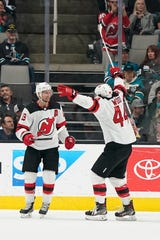 New Jersey Devils center Travis Zajac (19) celebrates with Miles Wood (44) after scoring a goal against the San Jose Sharks during the first period of an NHL hockey game Thursday, Feb. 27, 2020, in San Jose, Calif.