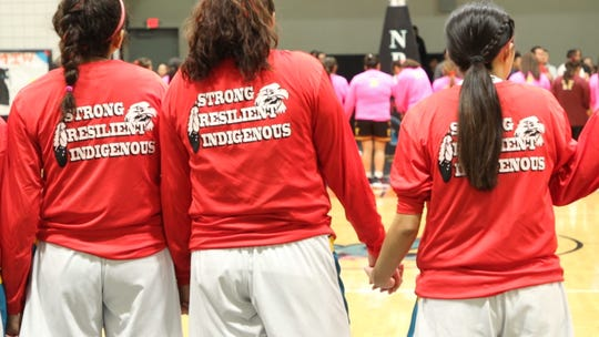 Members of Navajo Preparatory School's girls basketball team stand and show shirts in support of awareness of the MMIW epidemic at Navajo Prep's Eagles Nest gym in Farmington on Feb. 20, 2020.